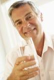 Mittlerer gealterter Mann, der ein Glas Wasser trinkt Stockfoto