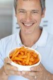Mittlerer gealterter Mann, der eine Schüssel Karotten anhält stockbilder