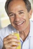Mittlerer gealterter Mann, der frischen Orangensaft trinkt Stockbild