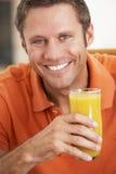 Mittlerer gealterter Mann, der frischen Orangensaft trinkt Stockfotografie