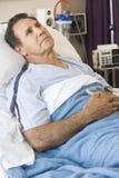 Mittlerer gealterter Mann, der im Krankenhaus-Bett liegt Stockfoto