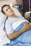 Mittlerer gealterter Mann, der im Krankenhaus-Bett liegt Lizenzfreies Stockfoto