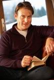 Mittlerer gealterter Mann, der mit dem Buch sitzt auf Sofa sich entspannt Lizenzfreie Stockbilder