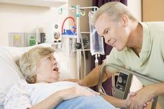 Mittlerer gealterter Mann, der mit Frau im Krankenhaus spricht lizenzfreie stockfotos
