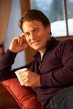 Mittlerer gealterter Mann, der mit heißem Getränk auf Sofa sich entspannt Stockfoto