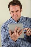 Mittlerer gealterter Mann, der Tablette-Computer verwendet Stockfotos