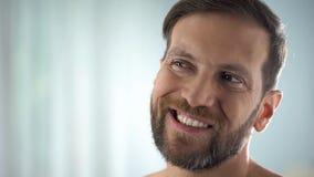 Mittlerer gealterter Mann, der Zähne vor Spiegel, zahnmedizinische Krankheit, Zahnfleischentzündung überprüft stockfotografie