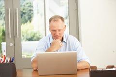 Mittlerer gealterter Mann, der zu Hause Laptop verwendet Stockbild