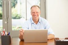 Mittlerer gealterter Mann, der zu Hause Laptop verwendet Stockfoto