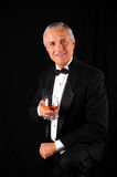 Mittlerer gealterter Mann in einem Smoking mit Weinbrandschallkanone Stockfotos