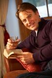 Mittlerer gealterter Mann mit Buch-trinkendem Whisky stockfotos
