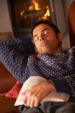 Mittlerer gealterter Mann schlafend mit Buch durch Cosy Protokoll-Feuer stockfotos