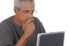 Mittlerer gealterter Mann und Laptop Stockbild
