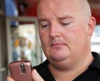 Mittlerer gealterter Mann unter Verwendung eines Handys Stockfoto