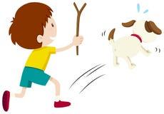 Mittlerer Junge, der einen Hund jagt Lizenzfreies Stockbild