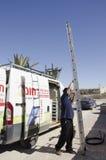 Mittlerer Ost-Mitzpe Ramon, Israel 29. Februar a-Arbeitskraft mit einer Leiter und Auto Lizenzfreie Stockfotos