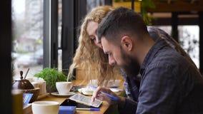 Mittlerer Schuss des Kerls und ein Mädchen besprechen ihren Start mit einer Tablette, die in einem Café sitzt stock footage