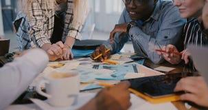 Mittlerer Schuss des multiethnischen kreativen vermarktenden Teams, das an Brainstorming hinter der Tabelle, schwarzes Angestellt stock video footage
