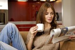 Mittlerer trinkender Kaffee der erwachsenen Frau und lesen Nachrichten Stockfotos