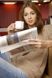 Mittlerer trinkender Kaffee der erwachsenen Frau und lesen Nachrichten Lizenzfreies Stockbild
