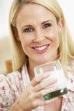 Mittleres erwachsene Frauen-Holding-Glas Milch Stockfoto