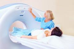 Mittleres erwachsenes medizinisches Personal, das Patienten zur Tomographie vorbereitet Lizenzfreie Stockfotografie