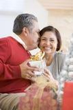 Mittleres gealtertes Paar-Sitzen und Holding-Weihnachten Stockfotografie