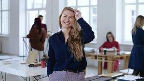 Mittleres geschossenes Porträt der glücklichen positiven jungen blonden Geschäftsfrau, die an der Kamera am modernen Dachbodenbür stock video footage