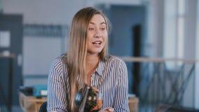 Mittleres geschossenes Porträt der jungen glücklichen schönen erfolgreichen kaukasischen Geschäftsfrau, die hinter Bürotisch auf  stock video footage