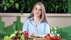Mittleres Nahaufnahmeporträt des lächelnden jungen Mädchens, das während frische Nahrung zu Hause kochen sich entspannt stock footage