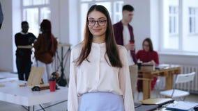 Mittleres Porträt der schönen jungen intelligenten brunette Geschäftsfrau in den Brillen, die Kamera im modischen Dachbodenbüro b stock video footage