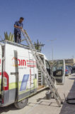 Mitzpe Ramon, Israel. February 29,A worker with a ladder on the roof of the car Royalty Free Stock Photos