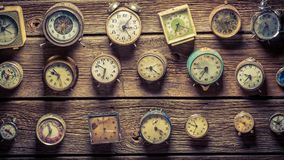 Mix of aged clocks on the wooden wall. Closeup of mix of aged clocks on the wooden wall royalty free stock photo