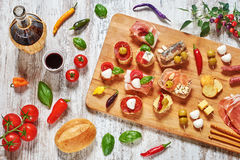Mix of appetizers / snacks / tapas on a wooden table. Mix of appetizers / snacks. Mediterranean tapas or antipasti on a rustic wooden table. Sandwiches with Royalty Free Stock Photo