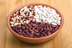 Mix of beans - red and white in a plate on a wooden table Royalty Free Stock Photo
