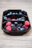 Mix of berries. Blackberries, raspberries and blueberries in a plastic plate Stock Images