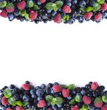 Mix berries and fruits at border of image with copy space for text. Ripe blueberries, blackberries, raspberries and black currants. On white background Stock Photo