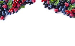 Mix berries and fruits at border of image with copy space for text. Ripe blueberries, blackberries, raspberries and currants on wh. Ite background. Background Stock Photo