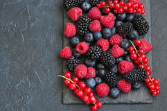Mix of berries raspberries red currants and blueberries on black. Slate board. Gray stone background.  Top view Royalty Free Stock Images