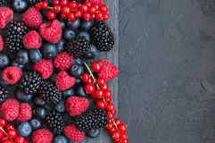 Mix of berries raspberries red currants and blueberries on black. Slate board. Gray stone background.  Top view Stock Photography