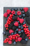 Mix of berries raspberries red currants blueberries and blackber. Ries on black slate board. White stone background.  Overhead view and copy space Stock Photo