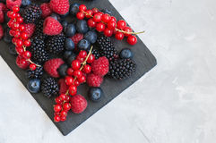 Mix of berries raspberries red currants blueberries and blackber. Ries on black slate board. White stone background.  Overhead view and copy space Royalty Free Stock Photos