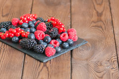 Mix of berries raspberries red currants blueberries and blackber. Ries on black slate board. Wooden background.  Close up and copy space Stock Image