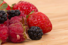 Mix of berries on a wooden table Royalty Free Stock Images