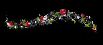 Mix of berry fruit in water splash, isolated on black background. Mix of berry fruit with mint leaves and ice cubes falling in water splash, isolated on black royalty free stock photo