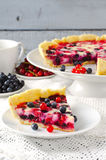 Mix berry tart, pie, cake with raspberries, bilberries, bluberries, red currant and cream on white background Stock Photos