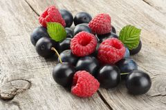 Mix blackthorn berries with raspberries and green leaf on old wooden table Stock Photography