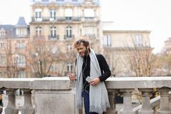 Mix blood music lover enjoying new earphones and smartphone  nea. Guy listening to music in white in ear headphones and new smartphone with Eiffel tower in Royalty Free Stock Photo