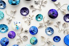 Blue and purple crystals and metal bees and flowers and dragonflies on white background Royalty Free Stock Images