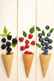 Mix of blueberries, blackberries, raspberries in ice cream cone on light wooden table. Background. top view with copy space Royalty Free Stock Images